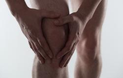 Young man touching his injured knee